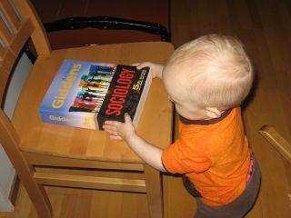 pieni poika pitää käsissään paksua sosiologian klassikkoa