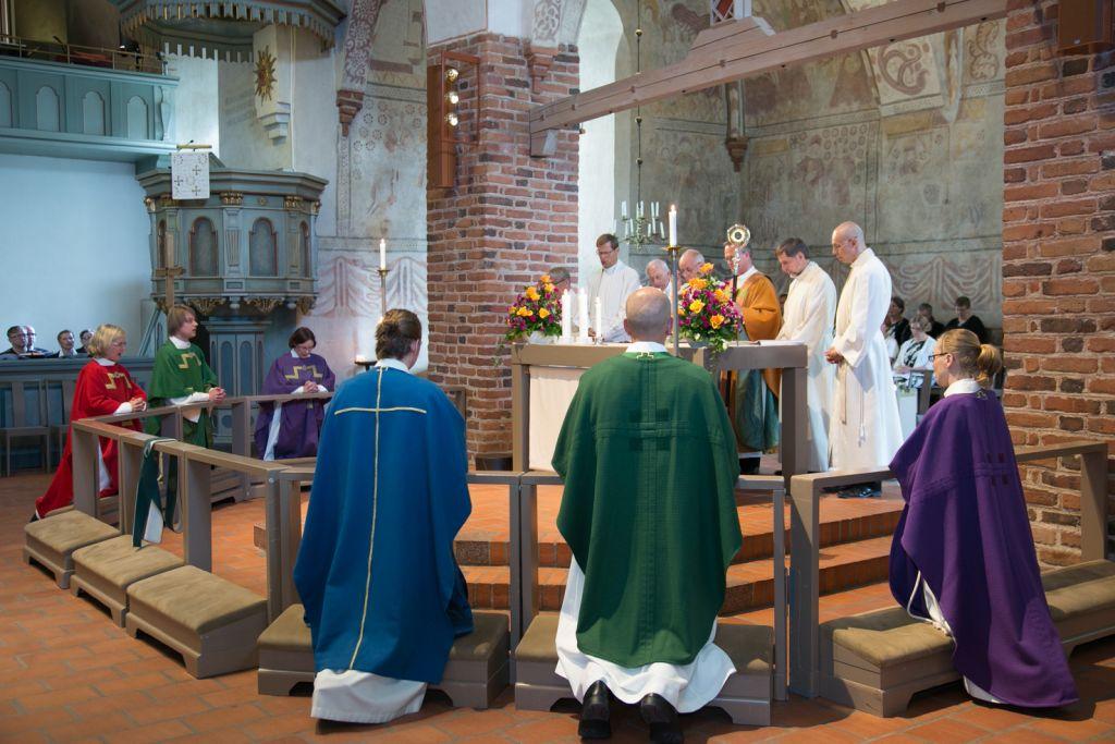 Papiksi vihityt polvistuneena tuomiokirkon alttarikaiteen ääreen