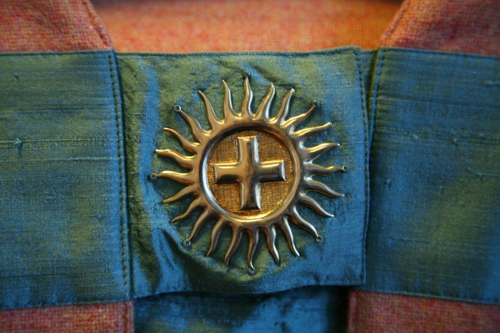 Piispan kasukan rintasolki, risti ja aurinko