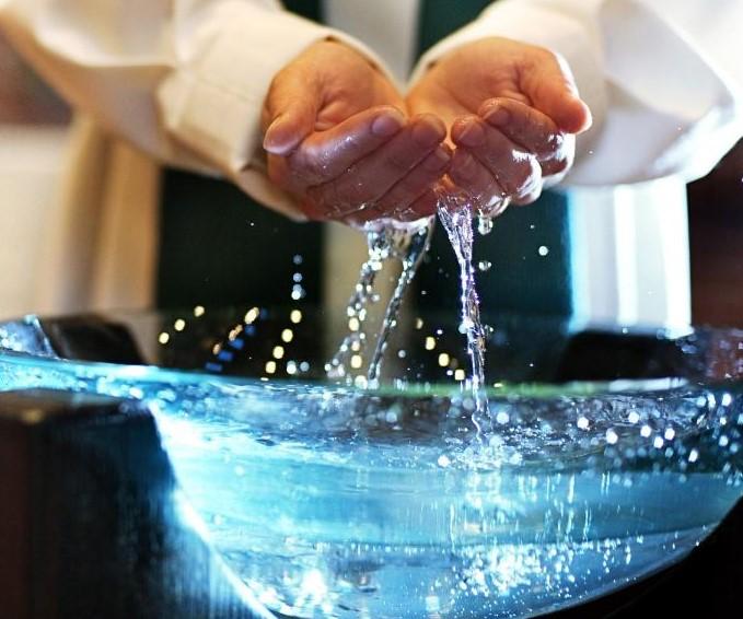 Lasinen kastemalja, josta pappi nostaa käsillään vettä