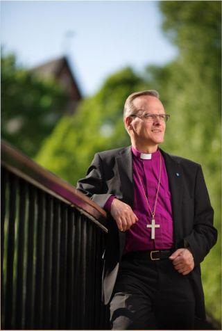 Piispa Tapio Luoman muotokuva, jossa piispa seisoo Espoon joen ylittävällä sillalla, taustalla näkyy Espoon tuomiokirkon pääty