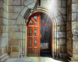 Avoin kirkon ovi, valosäteet oven yläpuolelta.