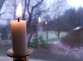 Valkoinen kynttilä metallisessa kynttilänjalassa ikkunalaudalla, kynttilän liekki heijastuu ikkunasta. Taustalla maalaismainen pihamaisema, maassa hieman lunta.