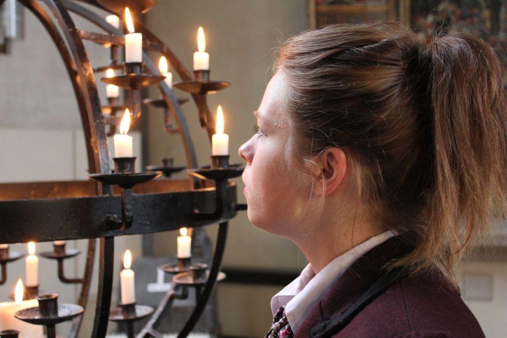 nuori nainen katsoo lähetyskynttelikköä