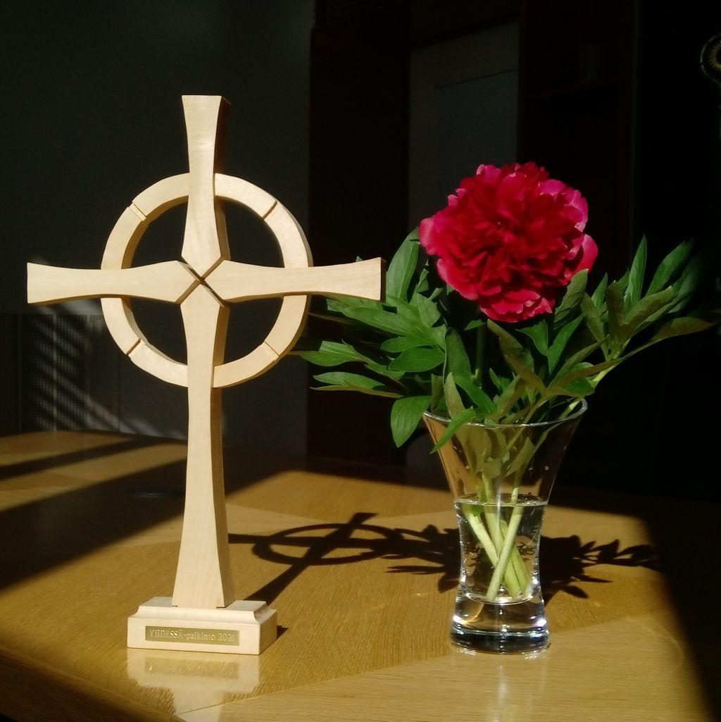 Yhdessä -palkinto, puinen kelttiristi auringonvalossa, vieressä punainen pioni